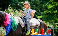 Regenbogental Patientin auf Pferd
